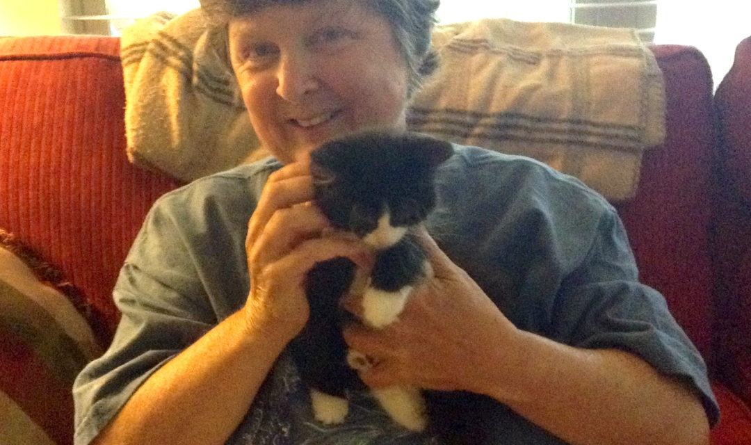Owner Deborah Murphy Holding A Black And White Kitten