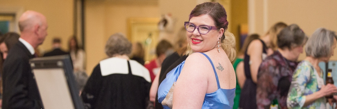 Tuxedo Cat Ball Attendee With Purple Cat Eye Glasses and Blue Dress Looking At Camera Over Her Shoulder